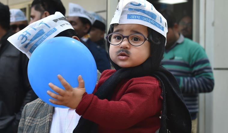 AAP workers hold a child dressed as Arvind Kejriwal as they celebrate party's victory in the Delhi Assembly polls, at party headquarters | Aayush Goel