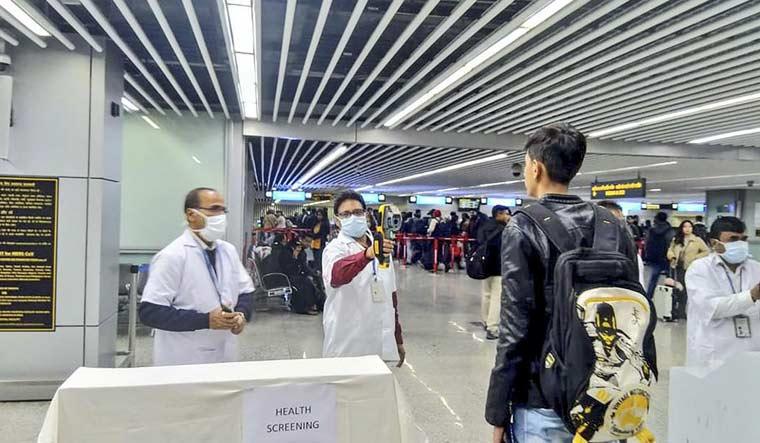 Officials use a thermographic camera to screen the head of a passenger at Netaji Subhash Chandra Bose International Airport in Kolkata | AFP