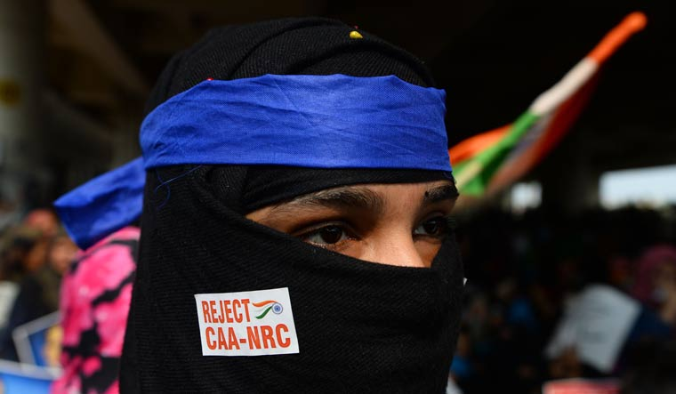 A demonstrator takes part in a protest against CAA and NRC at Jaffrabad in Delhi | AFP