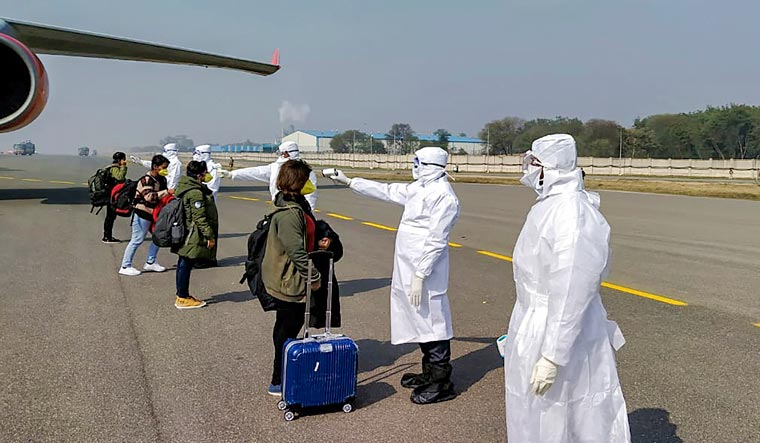 Medics screen Indian nationals after they were brought by an Air India aircraft from China's coronavirus-hit city of Wuhan, at the airport in New Delhi | PTI