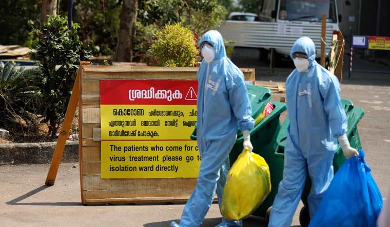 [File] Workers walk with garbage after cleaning an isolation ward at a hospital for observing people suspected to have coronavirus infection in Kochi | AP