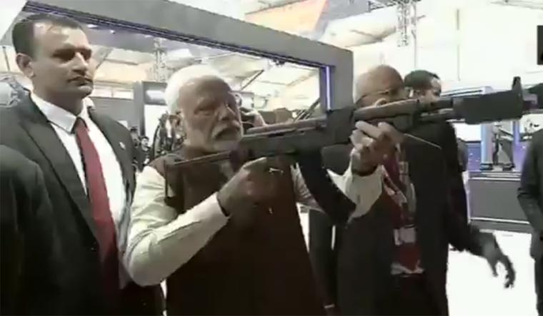 [Video grab] Prime Minister Narendra Modi taking aim with an assault rifle in his hand at a stall showcasing the virtual shooting range at the DefExpo 2020 in Lucknow