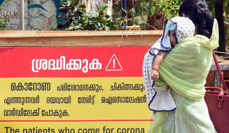 A woman with her child walks past a notice board outside Special Isolation Ward set up to provide treatment to novel coronavirus patients at a hospital in Kochi   PTI