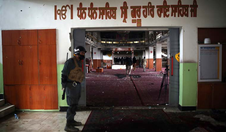 An Afghan policeman stands guard at the entrance to a Gurdwara, as journalists film the aftermath of an attack in Kabul | AP