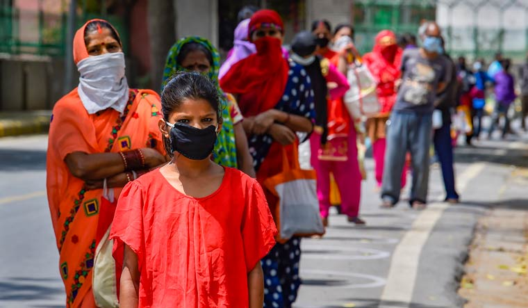 People wearing masks stand in a queue to collect food distributed by Delhi government volunteers during the ongoing coronavirus lockdown, in New Delhi | PTI