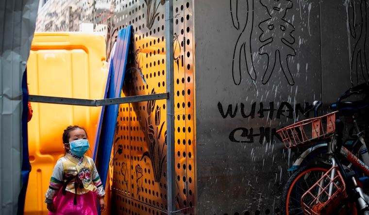 A girl wearing a face mask crosses a barricade in Wuhan | AFP