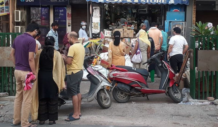 People waiting outside a shop in Lucknow to buy essentials after reports claimed that the government was sealing off the entire district.