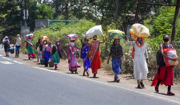 Migrants from Madhya Pradesh walk along a road towards their native places during the nationwide lockdown, in Surat | PTI