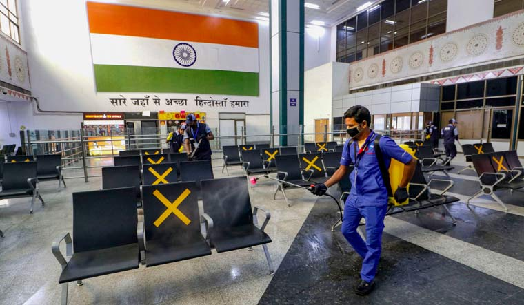 Airport staff disinfect Sardar Patel International Airport, during the fourth phase of COVID-19 nationwide lockdown, in Ahmedabad | PTI