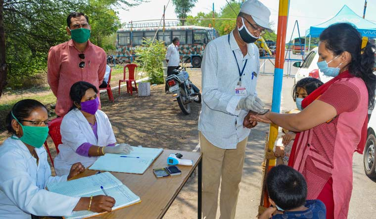A health worker marks 'home quarantine' with a stamp on a passenger travelling from Mumbai, during the ongoing COVID-19 nationwide lockdown, at Pune-Bangalore highway in Karad | PTI