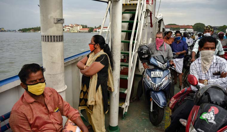 People wearing masks travel in a ferry during the coronavirus pandemic in Kochi | AP