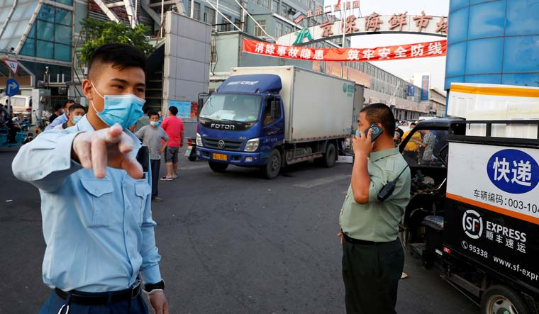 Security guards wearing face masks stand outside the Jingshen seafood market in Beijing | Reuters