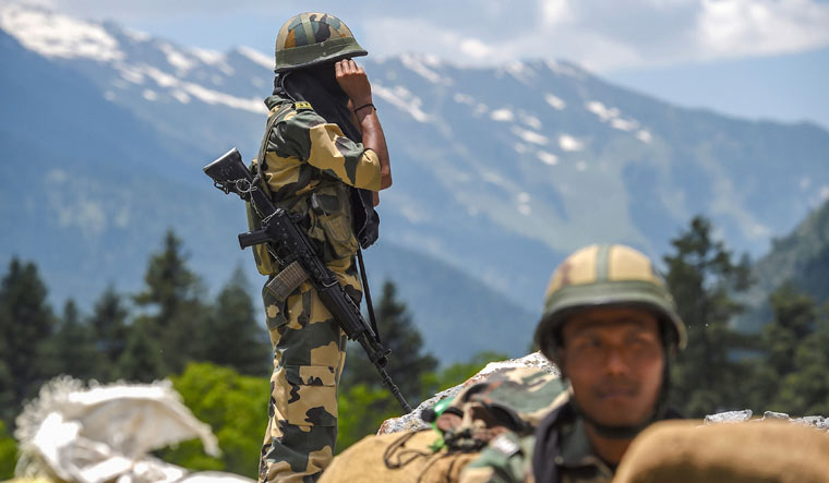 Border Security Force personnel stand guard along the Srinagar-Leh National highway, in Ganderbal district of Central Kashmir   PTI