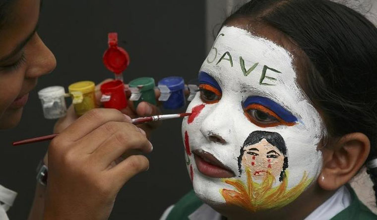 [File] A girl gets her face painted with an awareness message on female foeticide during a face-painting competition in Chandigarh | Reuters