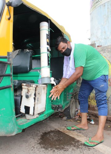 Mohammed Firoz washes his hands with the unit installed in his autorickshaw | Puja Awasthi