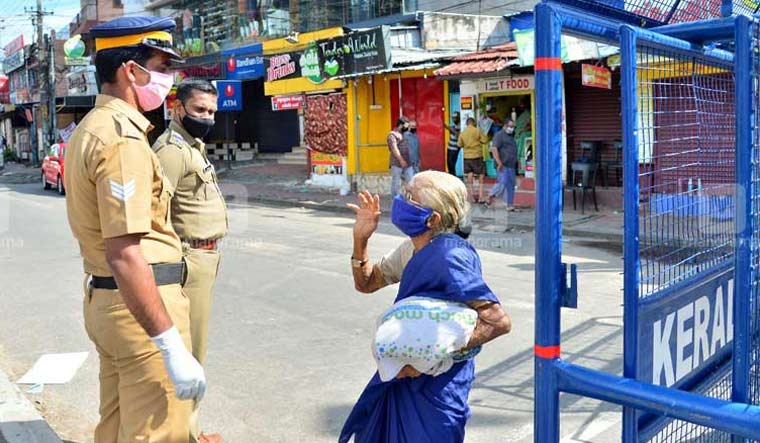An elderly woman speaks to police personnel near a barricade set up on a road to prevent movement of vehicles in Thiruvananthapuram | Manorama