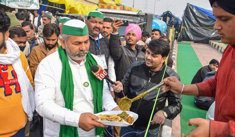 Bharatiya Kisan Union leader Rakesh Tikait having a meal on 'Makar Sankranti' during farmers' ongoing protest at Ghazipur border in New Delhi on January 14 | PTI