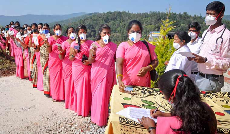 ASHA workers with their identity cards wait in a queue to get vaccinated with COVID-19 vaccine, at Kaimara in Chikmagalur | PTI