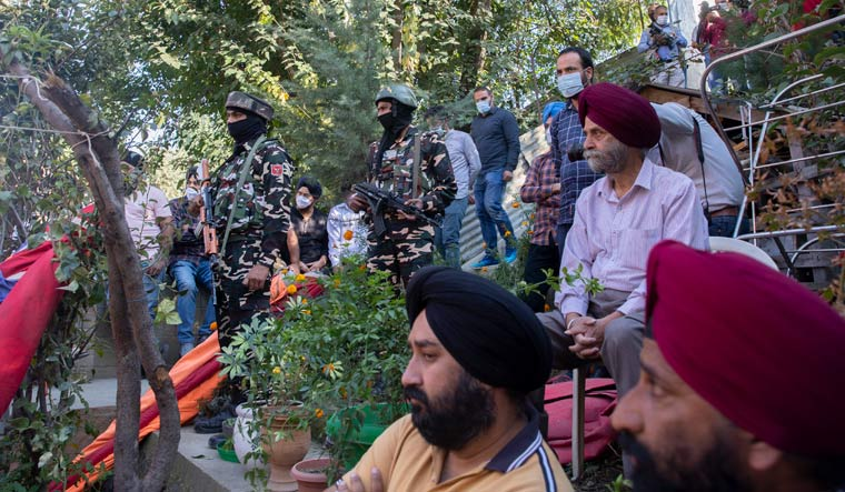 Paramilitary soldiers stand guard as relatives of Satinder Kour, one of two school teachers shot dead by assailants on Thursday, mourn outside her residence in Srinagar | AP