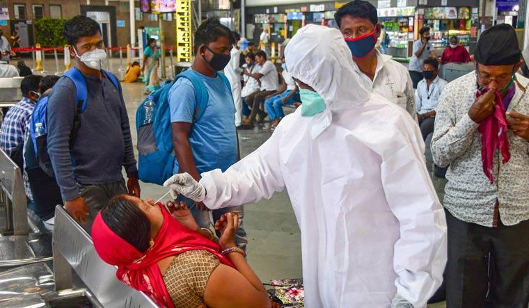 A health worker conducts COVID-19 testing of a passenger at Chhatrapati Shivaji Maharaj Railway Terminus, amid surge in coronavirus cases in Mumbai | PTI