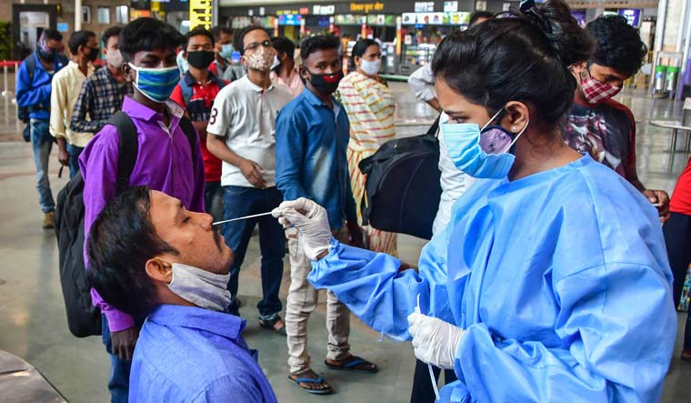 A health worker take swab samples of passengers at Chhatrapati Shivaji Maharaj Terminus Railway Station in Mumbai | PTI