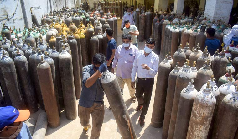 A worker sorts cylinders filled with medical oxygen at a plan in Prayagraj | PTI