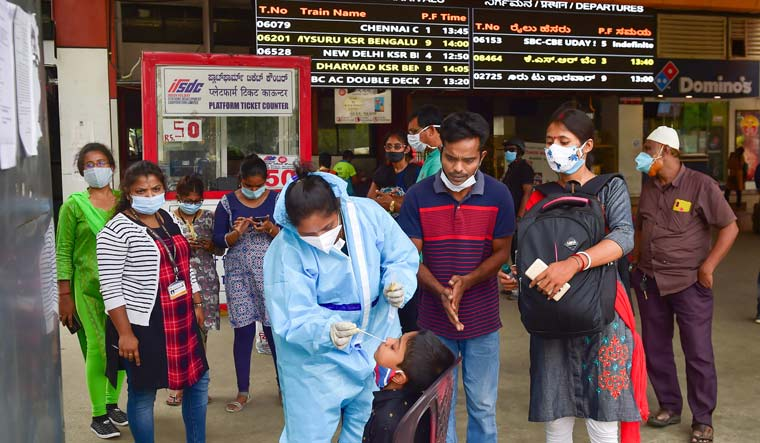 A medic collects samples for COVID-19 testing from a passenger at City Railway Station in Bengaluru | PTI