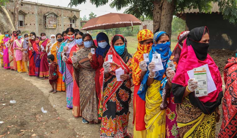 People stand in a queue to cast their votes during 6th phase of West Bengal Assembly Polls, in Burdwan | PTI