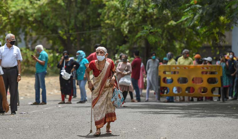 An elderly woman along with others waits to be vaccinated for COVID-19 in Mumbai | PTI