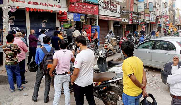 people-wait-queue-medicines-delhi-pti