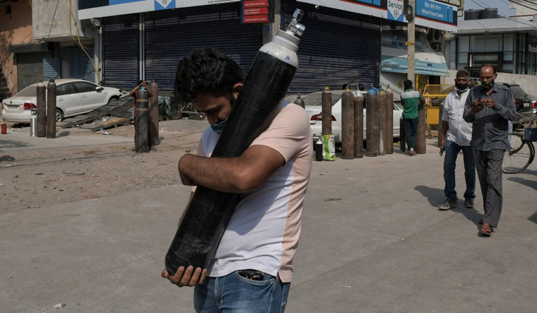 A man walks carrying a refilled cylinder at Mayapuri area in New Delhi | AP