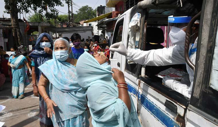 A medic conducts COVID-19 testing of slum dwellers in Bhopal | PTI