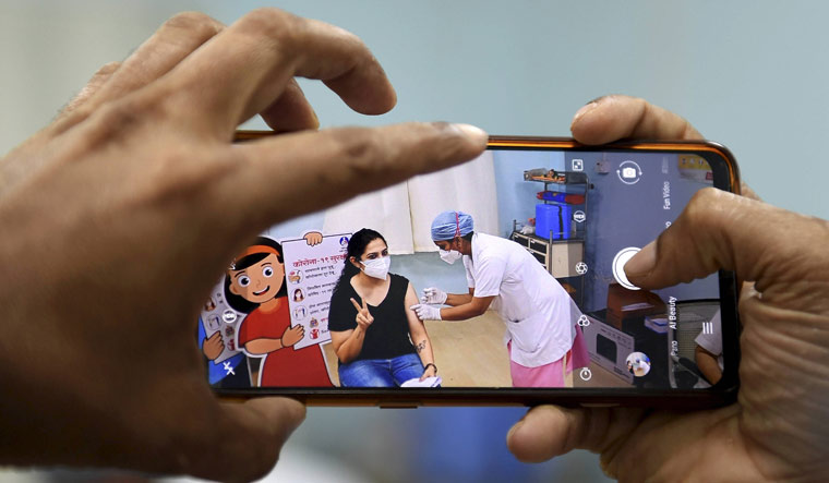 A man clicks a picture as a medic administers a dose of COVID-19 vaccine to a woman during the third phase of the inoculation drive, at Rajawadi Hospital in Mumbai   PTI