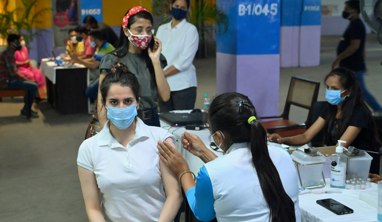 A medic administers COVID-19 vaccine at a walkthrough vaccination camp inside a mall in Gurugram   PTI