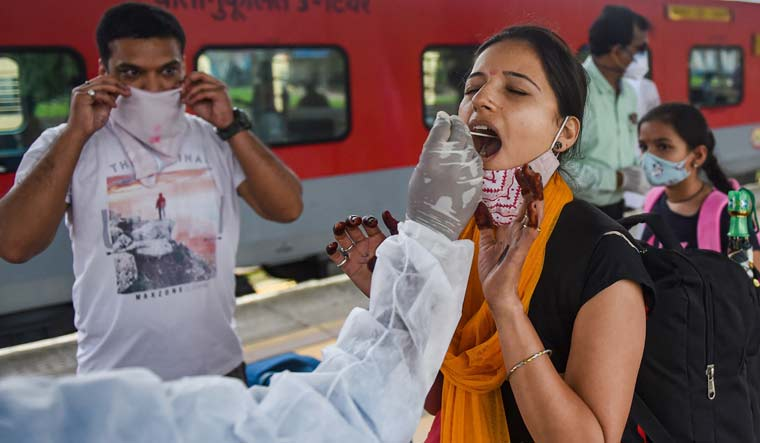 A BMC health worker collects swab sample of a passenger for COVID-19 test, at a station in Mumbai, Wednesday | PTI