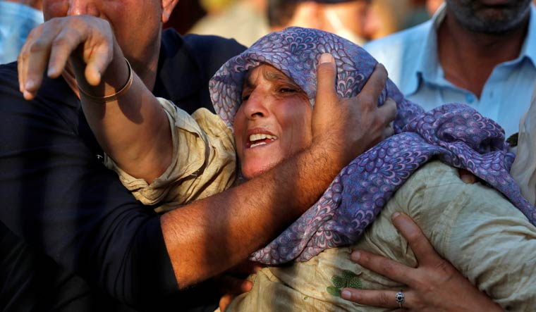 The mother of Arshid Ashraf Mir, a police officer who was killed by suspected militants, is consoled by her relatives during a wreath laying ceremony in Srinagar   Reuters