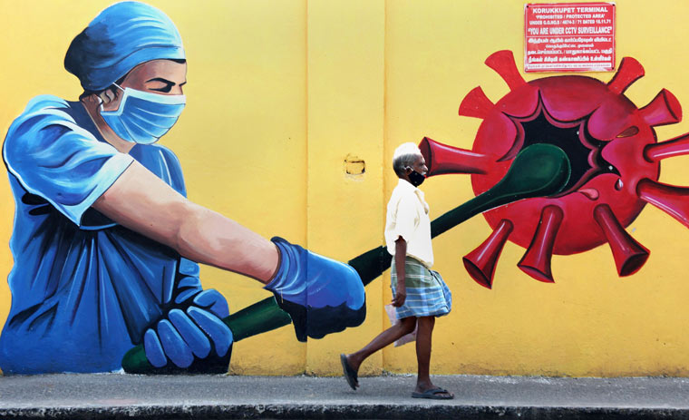 A man walks past a wall mural on COVID-19 awareness in Chennai | PTI