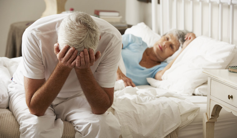 Worried-Senior-Man-Sits-On-Bed-Whilst-Wife-Sleeps-Erectile-dysfunction-shut