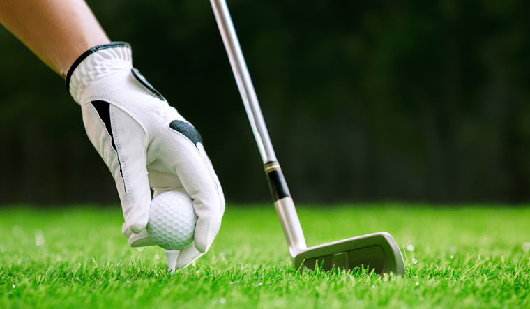 Golf-Hand-putting-golf-ball-on-tee-with-club-in-golf-course-shut