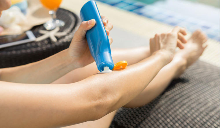 sunscreen-lotion-woman-poolside-shut