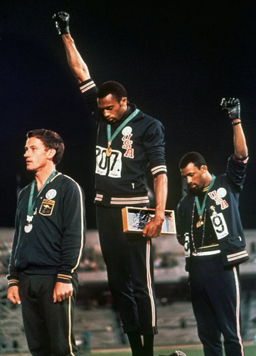[File] US athletes Tommie Smith (center) and John Carlos (right) stare downward while raising clenched fists which they called the 'human rights salute' | AP