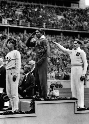 [File] Jesse Owens of the US (center) salutes during the presentation of his gold medal; Owens won four gold medals in the 1936 Summer Olympics in Berlin | AP