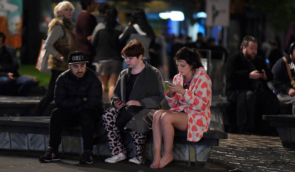 People evacuated from buildings along Dixon Street check their mobile phones while sitting on a bench in Wellington after a 6.6 earthquake based around Cheviot in the South island shock the capital