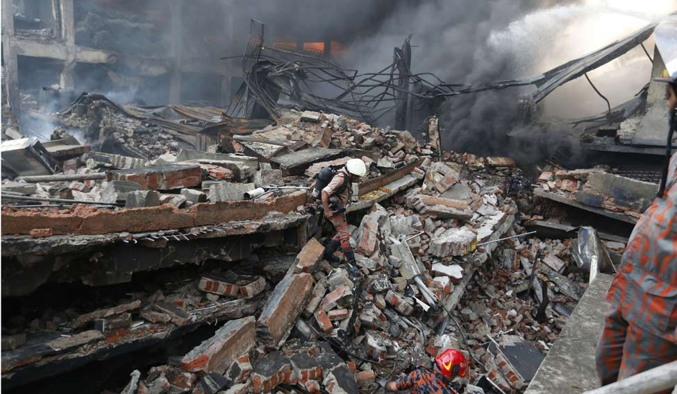 A firefighter walks on the rubble of a building at the site of a fire in Tongi industrial area outside Dhaka, Bangladesh