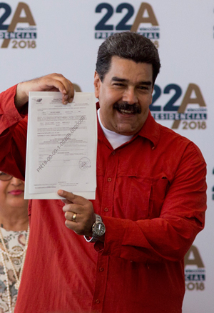 Venezuela's President Nicolas Maduro shows his presidential registration application to members of the press at the headquarters of the National Electoral Council (CNE) in Caracas | AFP