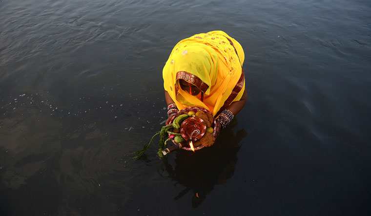 [File] A Nepalese Hindu woman makes offerings to the sun god in the Bagmati River in Kathmandu | AFP