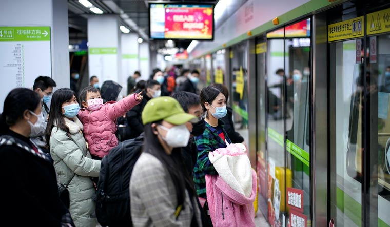 People wearing face masks wait for a subway train in Wuhan   Reuters