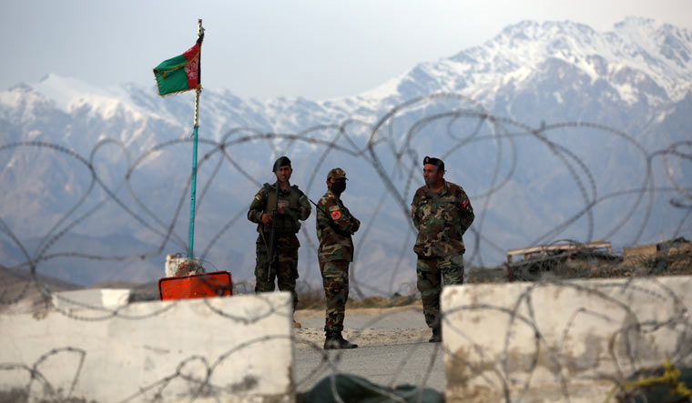 Afghan National Army soldiers stand guard at a checkpoint near the Bagram base in northern Kabul | AP