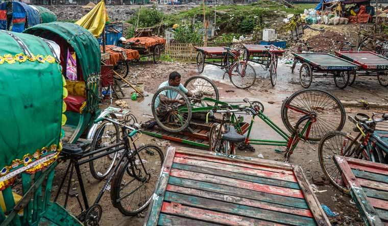 A labourer repairs a tricycle rickshaw at a garage in Dhaka | AFP