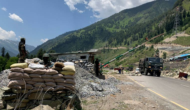 Indian paramilitary soldiers keep guard as an Army convoy moves on the Srinagar- Ladakh highway at Gagangeer | AP
